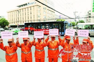 """几名环卫工人在阜南路与阜阳路交口,举起了粉红色的""""倡议牌""""。晨报记者 高博/摄"""