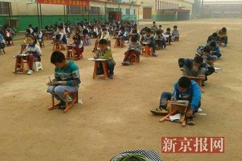小学生在重度霾天气下露天蹲着考试