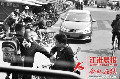 事发现场,刘师傅抱着生病的儿子与王师傅在路口争执。